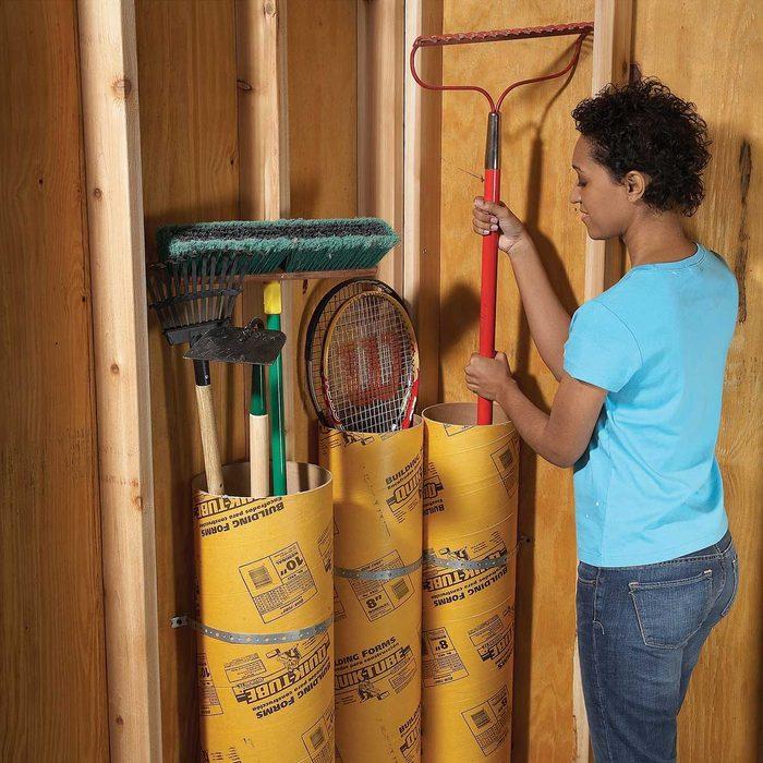 woman places a garden rake into a cardboard concrete tube in the garage