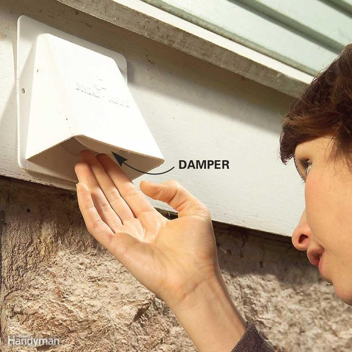 woman checks dryer vent damper