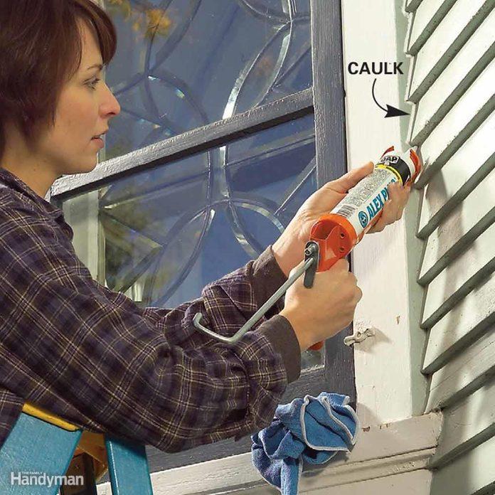 Woman caulks gap between trim and siding on a house