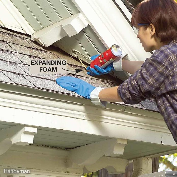 woman uses spray foam to seal gaps on a roof