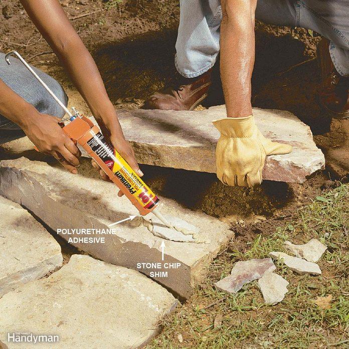 woman applies polyurethane adhesive to stone landscaping