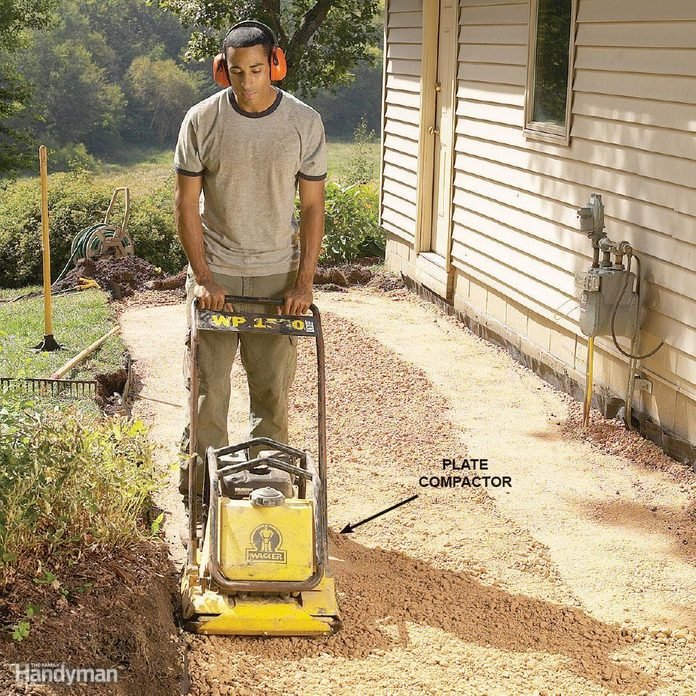 man operates a plate compactor along gravel in a backyard