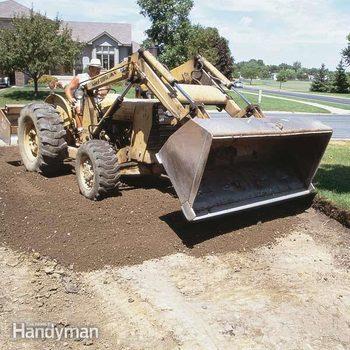 excavator drives over dirt to build an asphalt driveway