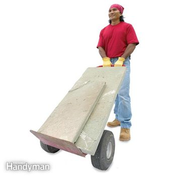 man uses a dolly to move large stones