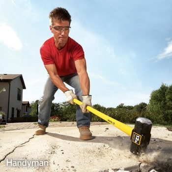 Man uses a sledghammer to break up concrete
