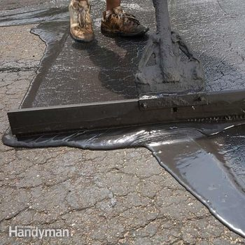 a squeegee pushes seal coat over a worn driveway
