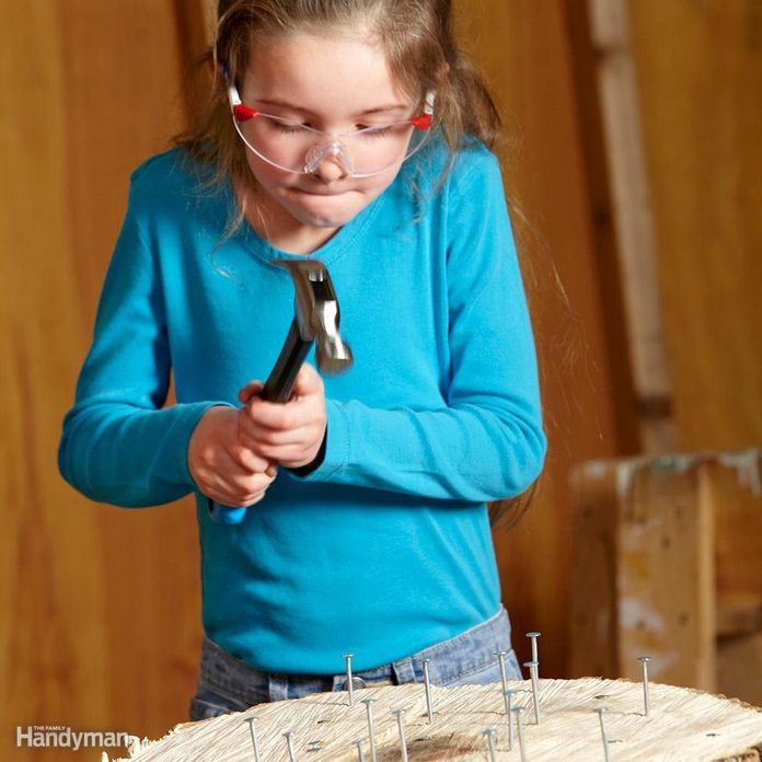 young girl uses hammer on nails in log