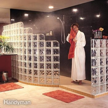Woman in a robe dries her hair after walking out of a glass block shower