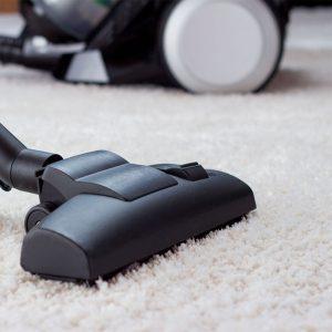 vacuuming white area rug