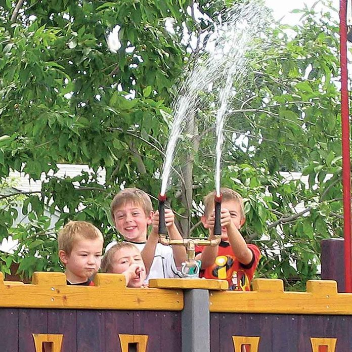 Children play with a water cannon on top of a treehouse