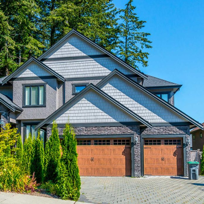 traditional home with dark trim and wooden garage doors