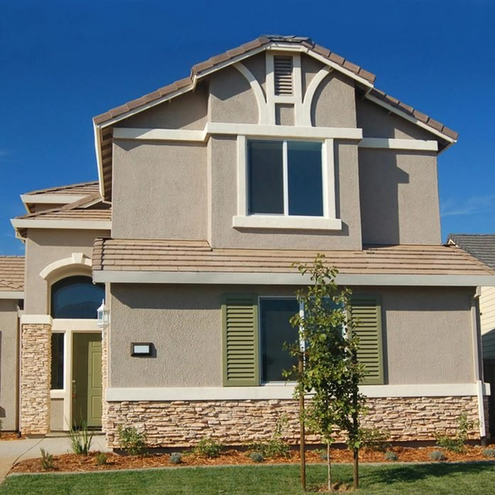 stucco home with white trim and green shutters