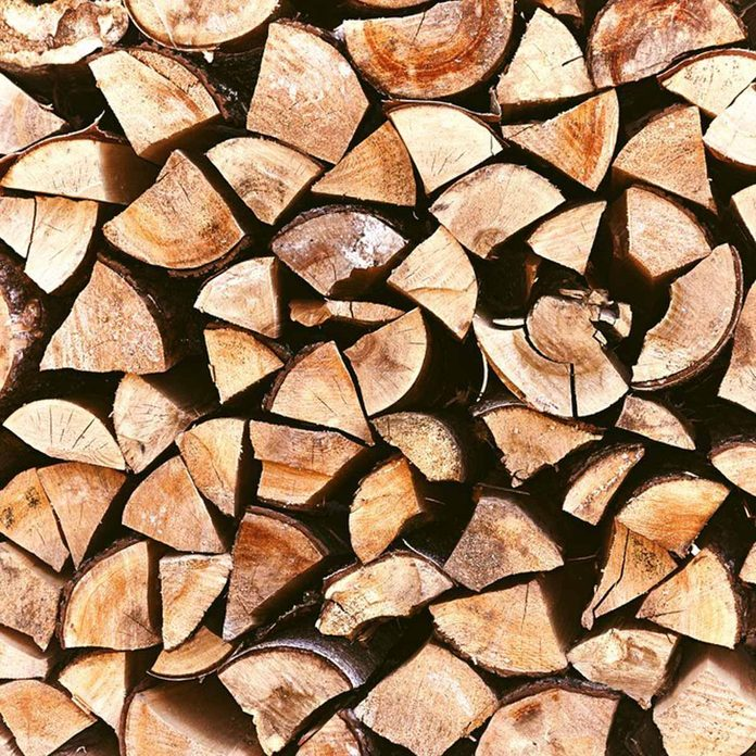 Pile of stacked triangle firewood prepared for fireplace and boiler.