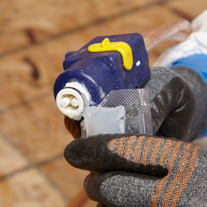 Lubing the tip of a spray foam gun   Construction Pro Tips