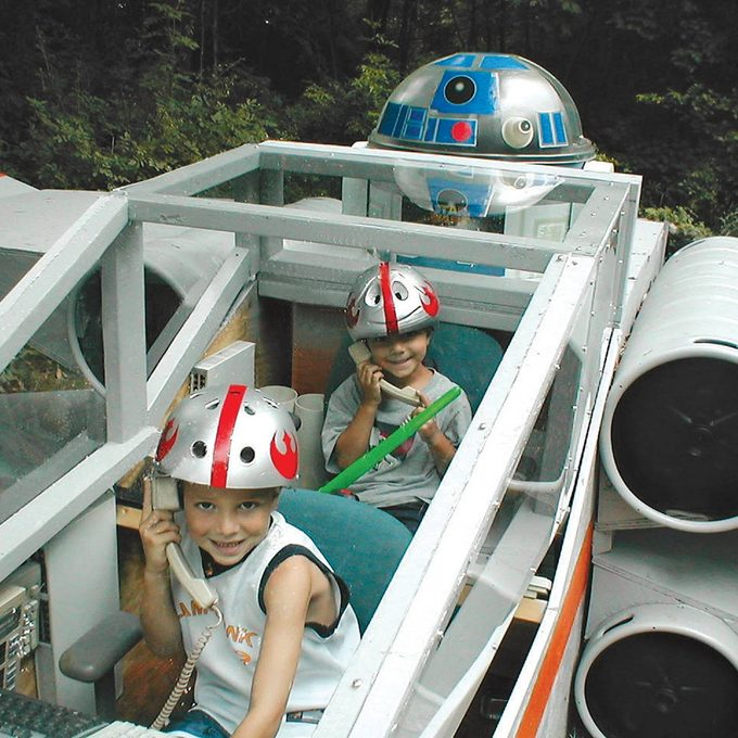 Kids playing in backyard X-wing star fighter jet