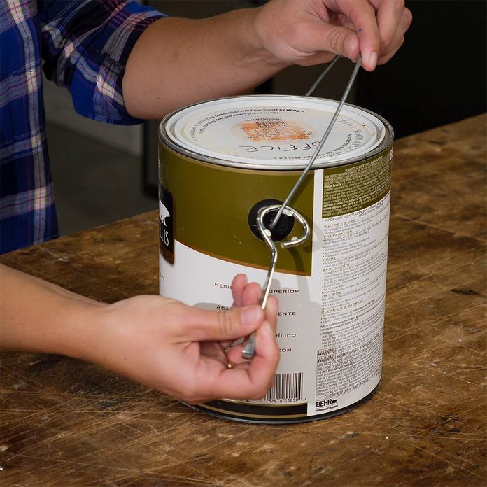 hooking paint can opener onto paint can handle