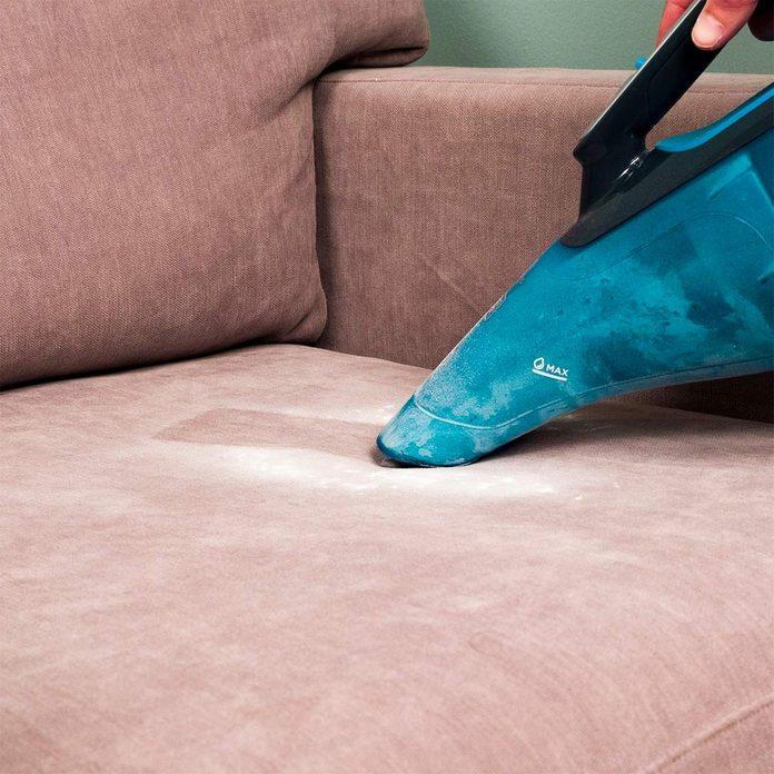 HH vacuuming up baking soda from upholstery