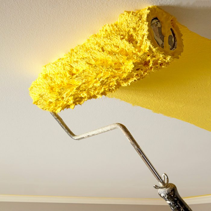 Rolling yellow paint onto a ceiling   Construction Pro Tips