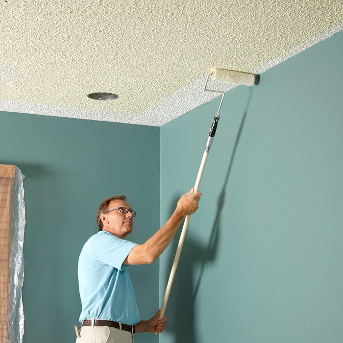 Man rolling darker paint onto a textured ceiling   Construction Pro Tips