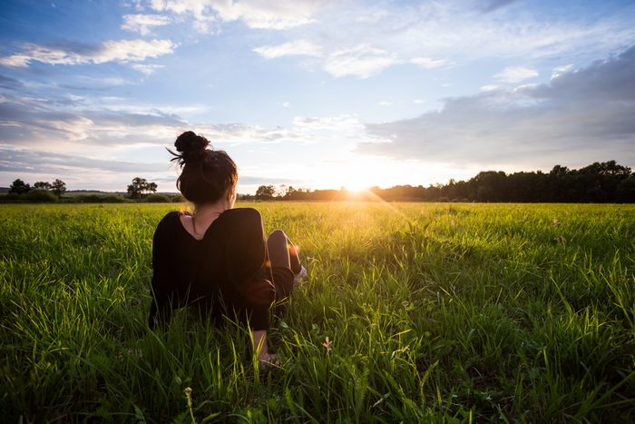 Woman in field watching sunset