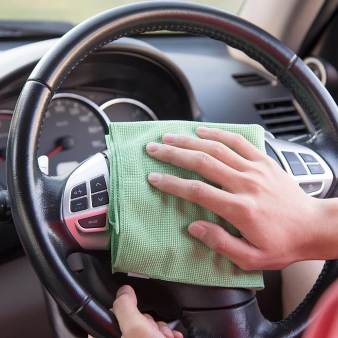 cleaning car interior with a rag steering wheel