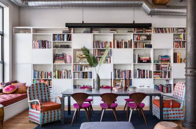 white bookcase with pink dining chairs