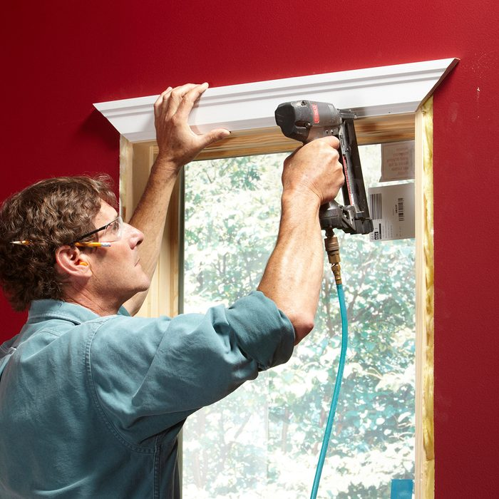 Stapling trim to the window for good spacing | Construction Pro Tips