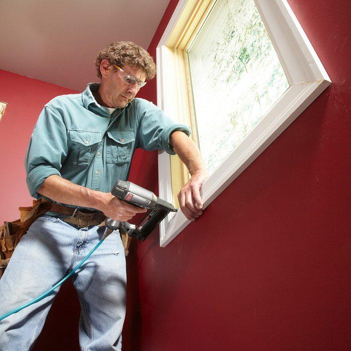 Man installing trim around a window | Construction Pro Tips