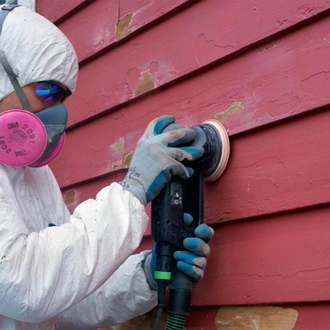 man sanding peeling paint on red house