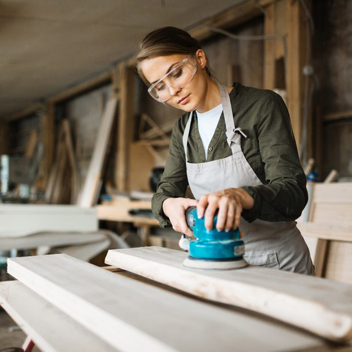 woman sanding with safety glasses