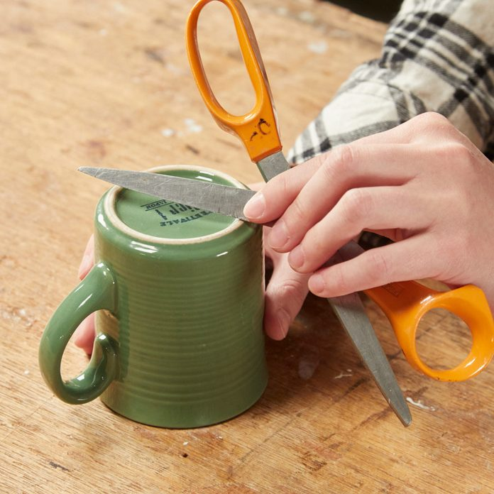 HH sharpening scissor blades on coffee mug