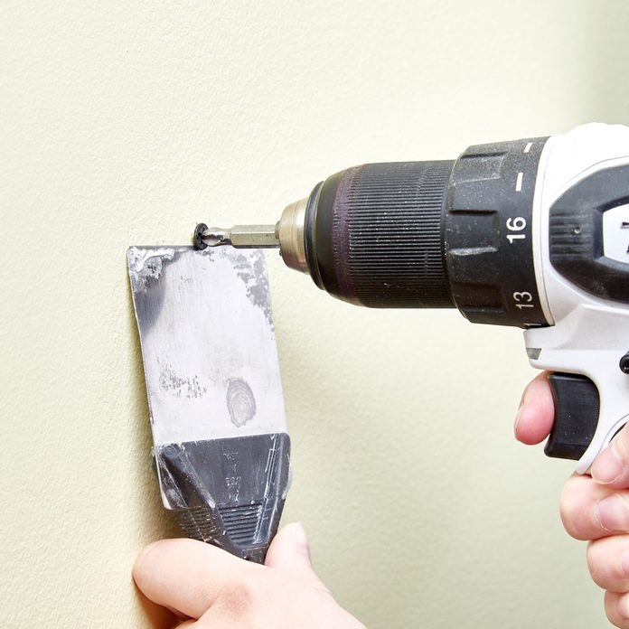 HH removing drywall screw with a putty knife