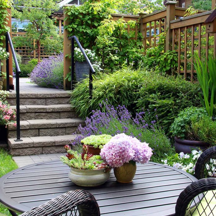 small yard landscaping with outdoor seating, grenery and potted plants