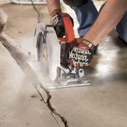 Man uses a saw to cut concrete