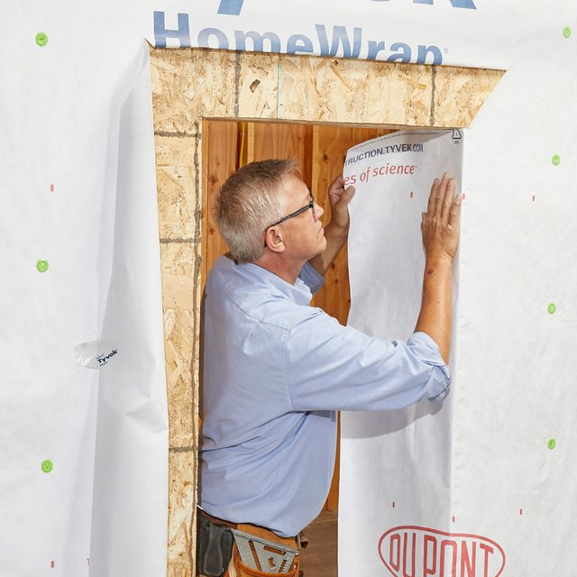 Man folding in the sides of the Tyvek   Construction Pro Tips