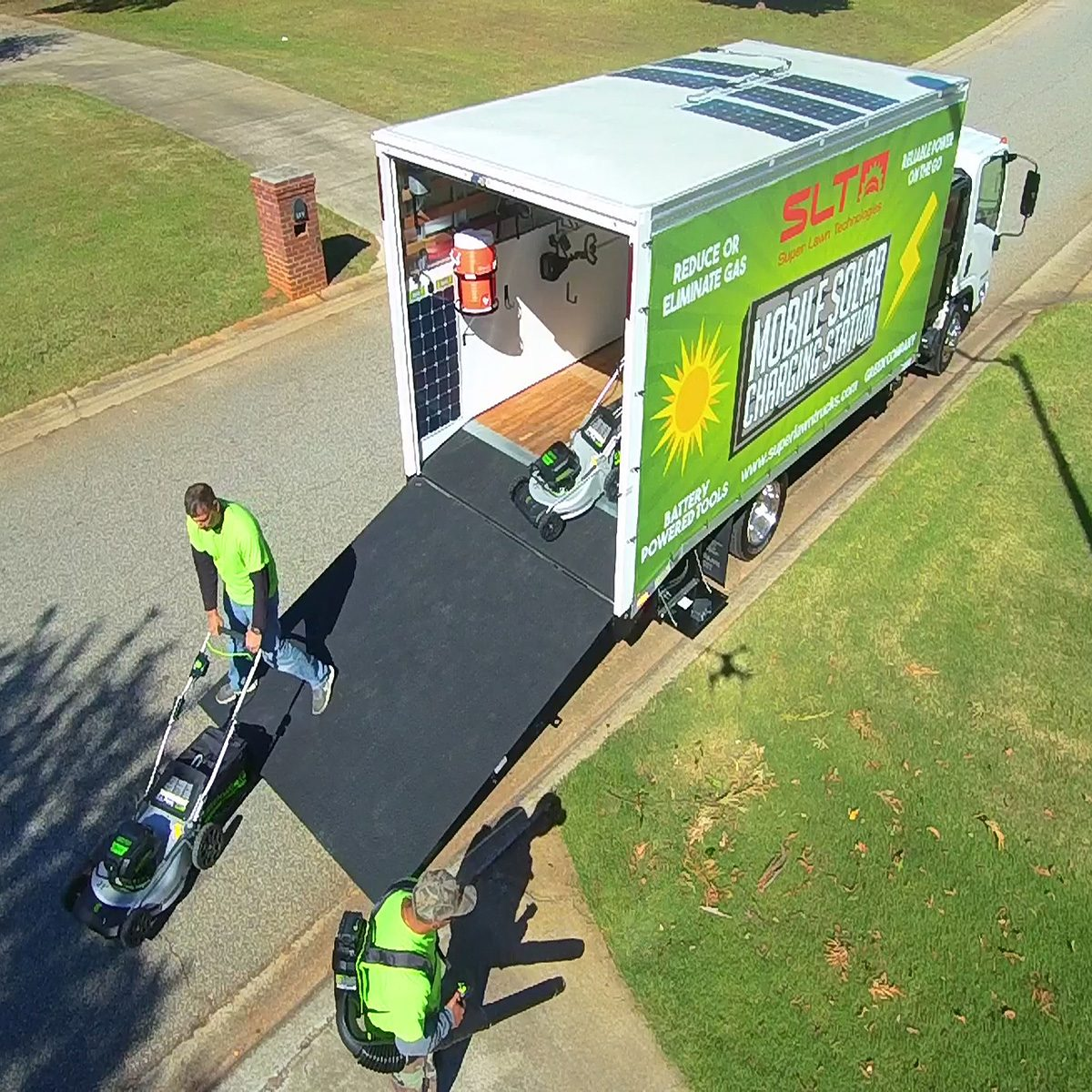 People removing landscaping equipment from Greenwork's solar truck | Construction Pro Tips