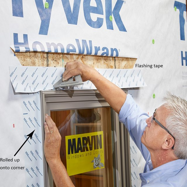Man taping the flanges of a window down during install   Construction Pro Tips