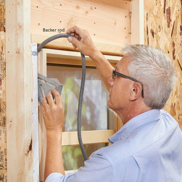 Man installing backer rod in window cavities   Construction Pro Tips