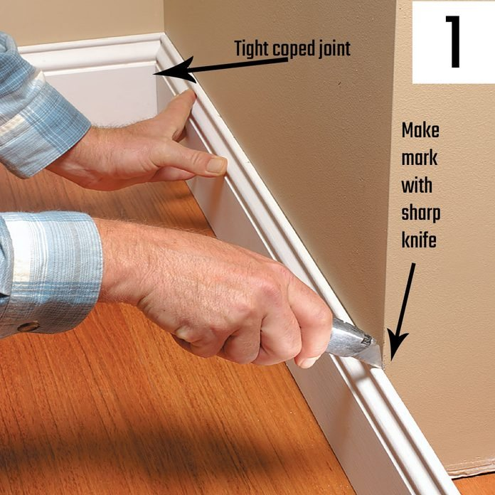 Marking a piece of trim with a utility knife | Construction Pro Tips