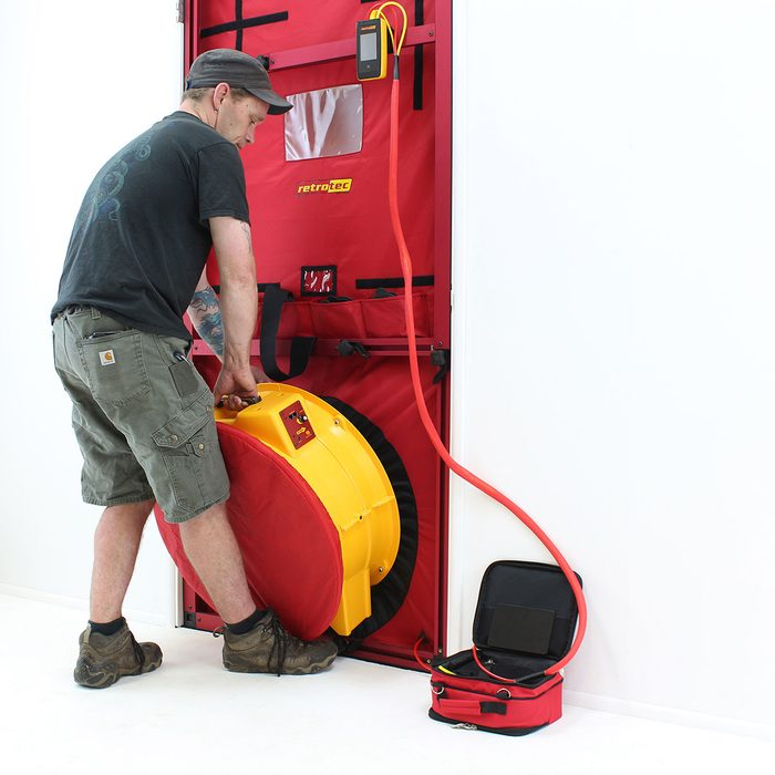 Putting a fan in place for a blower door test | Construction Pro Tips