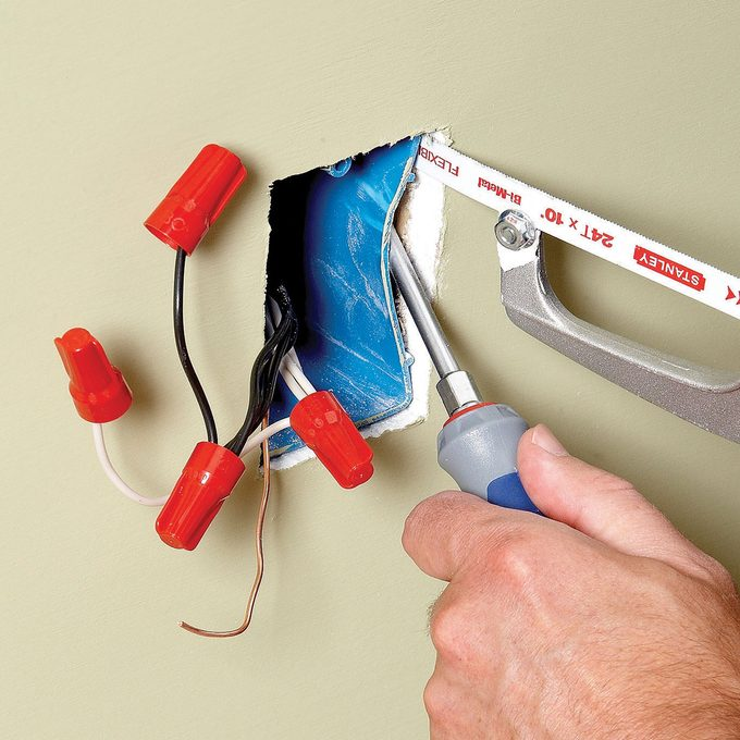 Pushing in an electrical outlet box with a screwdriver | Construction Pro Tips