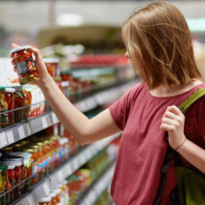 Sideways shot of pretty young female customer holds canned goods in glass container