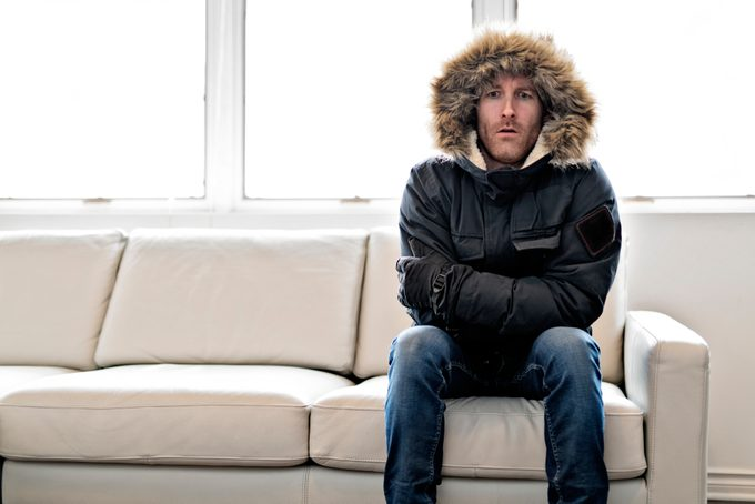 man in winter coat sitting on couch