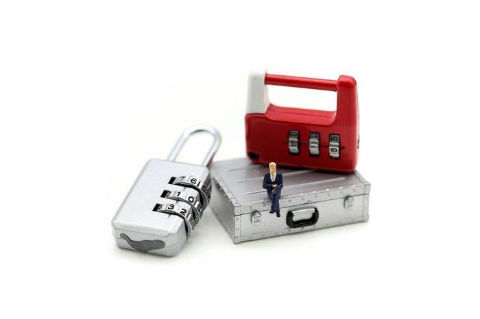 Miniature people : businessman sitting on metal security lock key.