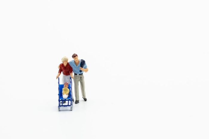 Miniature people, family and children isolated on white background. International Day of Families