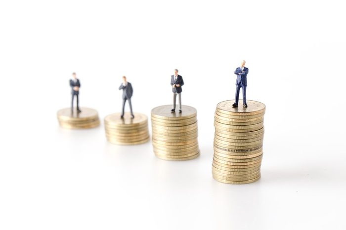 miniature model group of businesspeople standing together with coin isolated on white background.