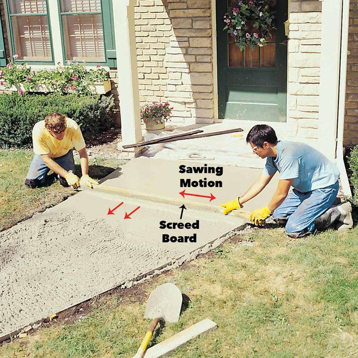 Level concrete sidewalk and flatten with a screed board