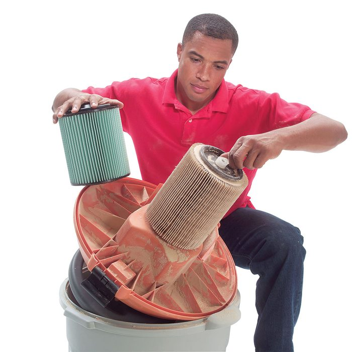 Man removing a filter and replacing it with HEPA filter | Construction Pro Tips