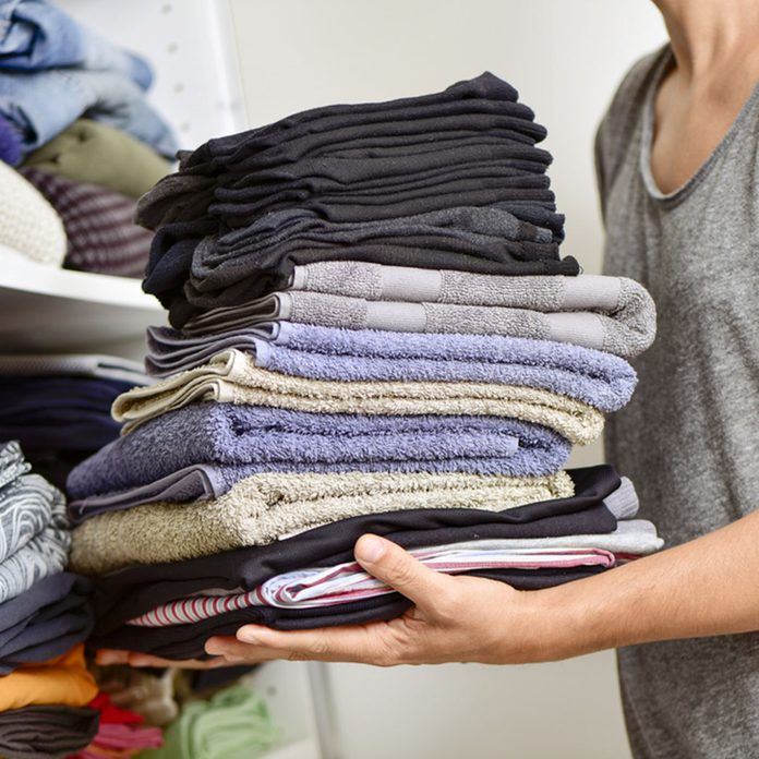 closeup of a young man carrying a pile of different folded clothes; Shutterstock ID 331641839; Job (TFH, TOH, RD, BNB, CWM, CM): Taste of Home