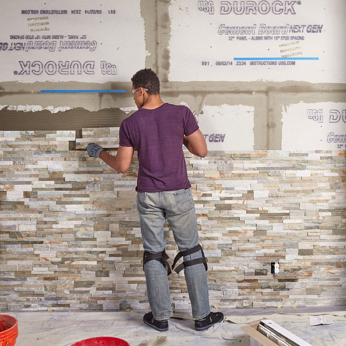Laying the stone further and further up the wall | Construction Pro Tips